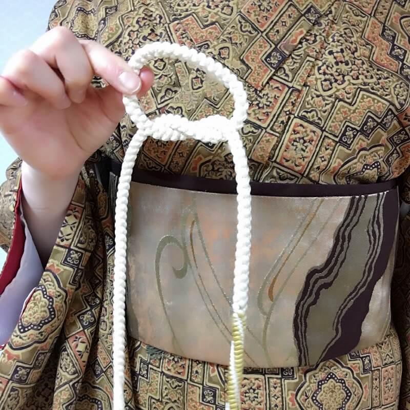 玉結びする要領で、帯締めの先端を輪っかの中に通します。